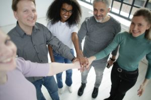 Happy diverse co-workers joining hands